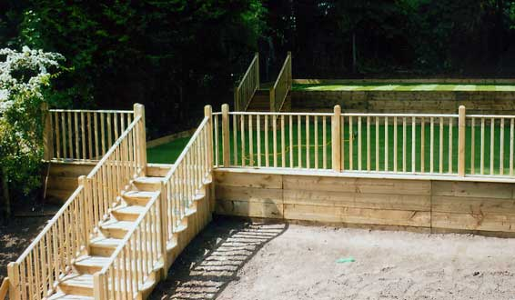Wooden steps and handrail leading turfed lawn with balustrades